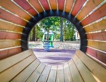 Se igenom det tomma wood röret på lekplatsen för barn, på grön äng Royaltyfri Bild