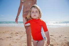 Se innehavhanden för litet barn av modern på stranden Arkivbild