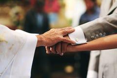 Se mariant, mains de la jeune mariée, marié et prêtre dans une église mexicaine à Mexico photos stock