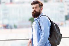 Se mer brutal Brutal caucasian man med det långa skägget på stads- bakgrund Bärande ryggsäck för brutal hipster i tillfälligt arkivfoto