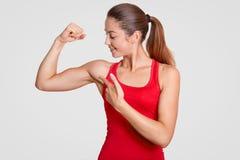 Se min biceps! Den starka unga gulliga kvinnan går in för sport, har den starka kroppen, visar henne muskler, den iklädda röda t- arkivfoton