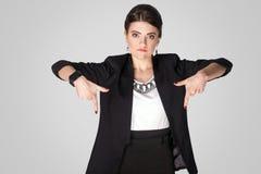 Se ner nu! Allvarligt kvinna som ner pekar fingret Royaltyfri Foto