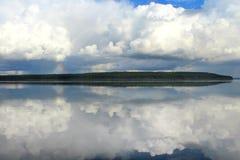 Se nubla blanco en el cielo azul con un pequeño arco iris con la reflexión en el lago durante el día en el environtent natural Imagen de archivo libre de regalías