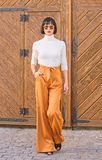 Se?ora alta delgada del equipo de moda concepto de la moda y del estilo Paseo de la mujer en pantalones flojos Morenita de moda d fotografía de archivo