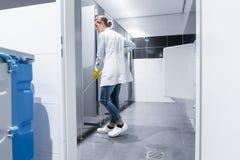 Se?ora de la limpieza o portero que aljofifa el piso en lavabo imagenes de archivo