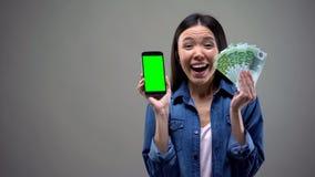 Se?ora joven emocionada que sostiene los billetes de banco del smartphone y del euro, ganador de loter?a en l?nea foto de archivo