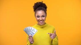 Se?ora joven sonriente que se?ala en los billetes de banco del d?lar a disposici?n, cr?dito de banco, ganancias fotografía de archivo libre de regalías