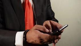 Se permite al hombre de negocios en esposas hacer una llamada de teléfono almacen de video