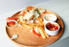 Se pierde Junk Food o comida estropeada y otra basura, en los di de madera Imagen de archivo