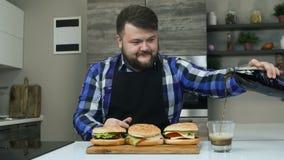 Se preparan las hamburguesas El hombre regordete alegre vierte el refresco carbónico en un vidrio Forma de vida malsana, frita y metrajes