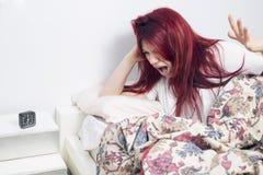 Se réveiller fâché de femme, se trouvant sur le lit éveillé Image stock