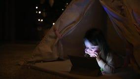 Se reposant à la maison dans une tente dans la perspective d'un arbre de Noël, une petite fille se trouvant sur les bandes dessin banque de vidéos