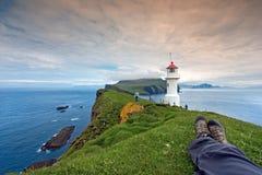 Se reposant après la hausse au phare de Mykines, les Iles Féroé Photographie stock