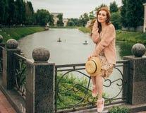 se repose sur une barrière, dans les mains d'un chapeau, d'une robe beige en fleur et d'un chandail beige Belle fille red-haired  photo stock