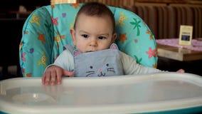 Se reposer caucasien mignon de bébé sérieux et calme sur une chaise d'arbitre en café 4k banque de vidéos