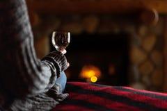 Se reposer dans la cabine confortable par la cheminée de fieldstone avec le verre de vin photo stock