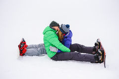 Se reposer de baiser de garçon et de fille sur la neige Photographie stock libre de droits
