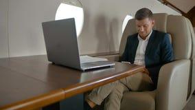 Se reposer de causerie d'homme d'affaires dans le fauteuil confortable dans la carlingue de jet privé banque de vidéos