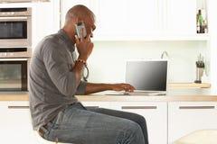 Se reposer de détente d'homme dans la cuisine parlant au téléphone Photos stock
