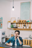 Se reposer de détente de jeune homme dans la cuisine parlant au téléphone image stock