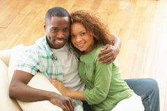 Se reposer de détente de jeunes couples romantiques sur le sofa Image stock