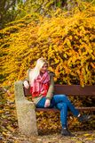 Se reposer de détente de femme sur le banc en parc automnal images stock