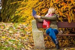 Se reposer de détente de femme sur le banc en parc utilisant le comprimé Images libres de droits