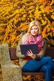 Se reposer de détente de femme sur le banc en parc utilisant le comprimé photos stock
