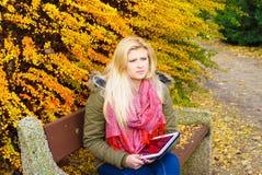 Se reposer de détente de femme sur le banc en parc utilisant le comprimé photos libres de droits