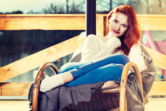 Se reposer de repos de femme rousse d'Atractive sur la chaise de basculage dans f image libre de droits
