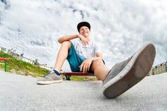 Se reposer de repos de jeune patineur sur sa planche à roulettes dans un skatepark Images stock