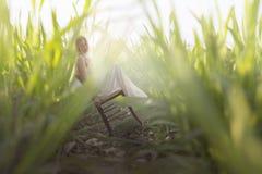 se reposer de repos de femme miniature parmi les touffes gigantesques de l'herbe image libre de droits