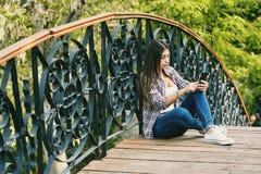 Se reposer de repos de jeune femme sur un pont en bois Image stock