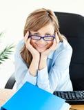 Se reposer de sourire de femme d'affaires avec du charme à son bureau Photographie stock