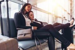 Se reposer femelle de sommeil de deux amis sur des chaises dans l'aéroport Images stock