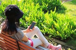 Se reposer femelle sur le banc en bois dans le jardin vert vibrant tenant un téléphone portable dans sa main photographie stock