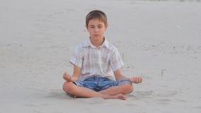 Se reposer méditant de garçon sur le sable sur la plage en été clips vidéos