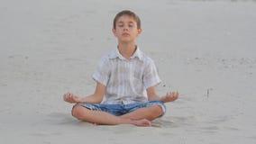 Se reposer méditant de garçon sur le sable sur la plage en été banque de vidéos