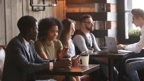 Se reposer parlant africain de jeune homme et de femme à la table de coffeeshop banque de vidéos