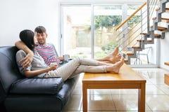 Se reposer parlant de couples attrayants heureux sur le divan dans h moderne Photographie stock