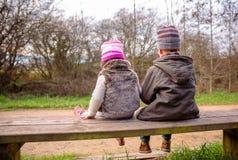Se reposer parlant de garçon et de petite fille sur un banc Photos libres de droits