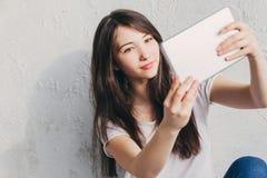 Se reposer près du mur et regards dans la Tablette Image stock