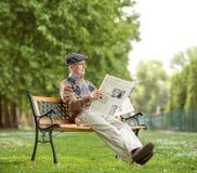 Se reposer supérieur lisant un journal en parc Photographie stock