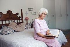 Se reposer sur son lit lisant un livre Photos libres de droits