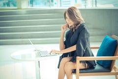 Se reposer travaillant d'entrepreneur féminin à un bureau Photographie stock libre de droits