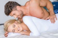 Süße sexy kaukasische Paare, die auf weißem Bett liegen Lizenzfreie Stockfotos