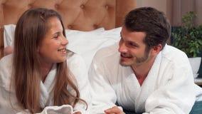 Se situer parlant de couples affectueux heureux dans le lit utilisant ensemble des peignoirs banque de vidéos