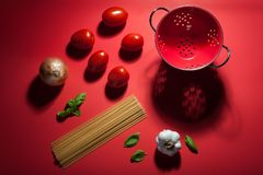 Se som är rött - framställning av pastasås En deconstructed plats som visar de van vid ingredienserna, gör pasta och sås royaltyfri bild