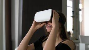 Se sorprende la muchacha feliz atractiva utiliza los vidrios del vr almacen de metraje de vídeo