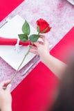 Se tenir de mains de femme a monté au-dessus de la table décorée Images stock